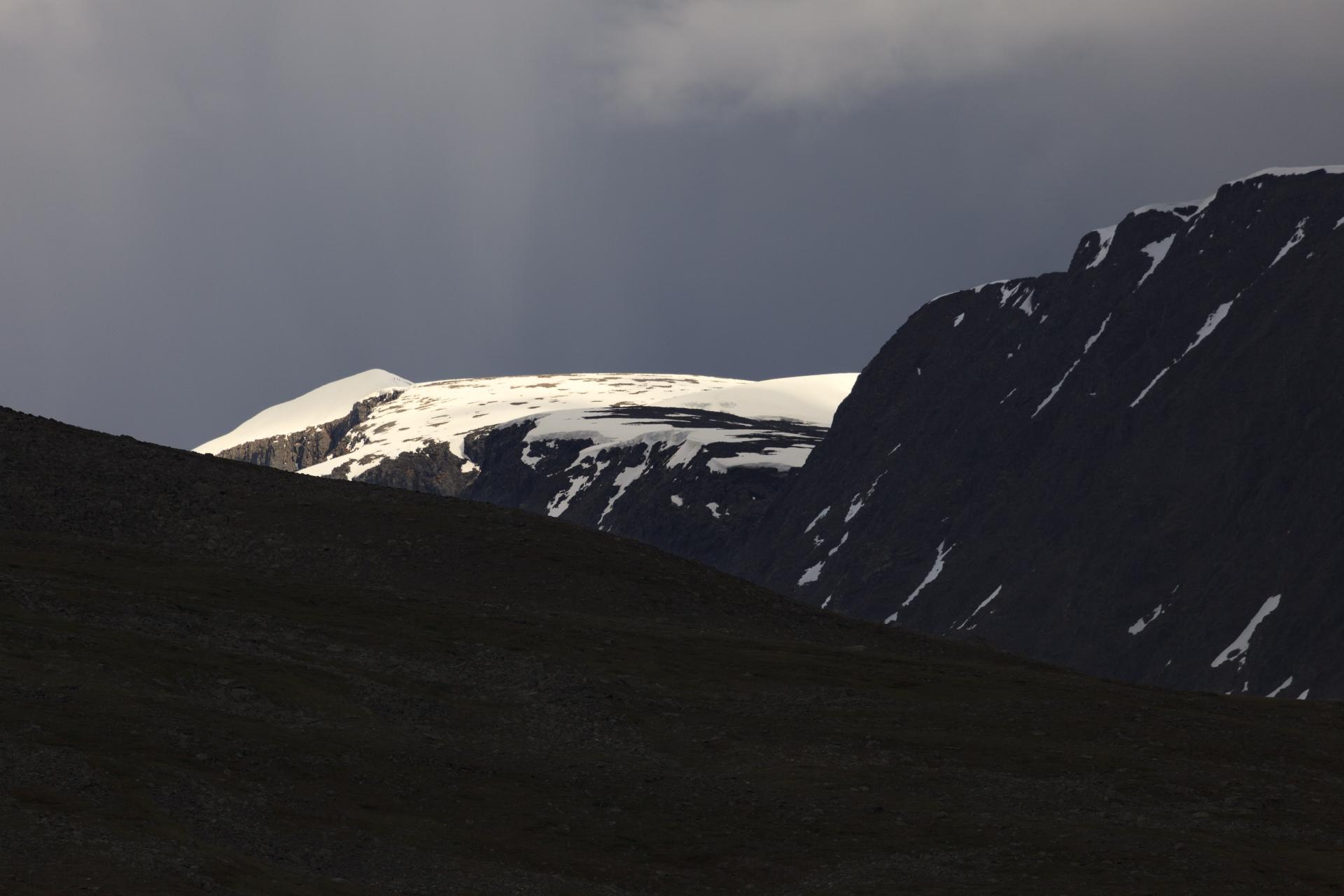 Mitten im Gewitter, bei strömendem Regen, taucht in der Ferne die Gipfelpyramide des Kebnekaise auf – dort oben wollen wir morgen stehen!