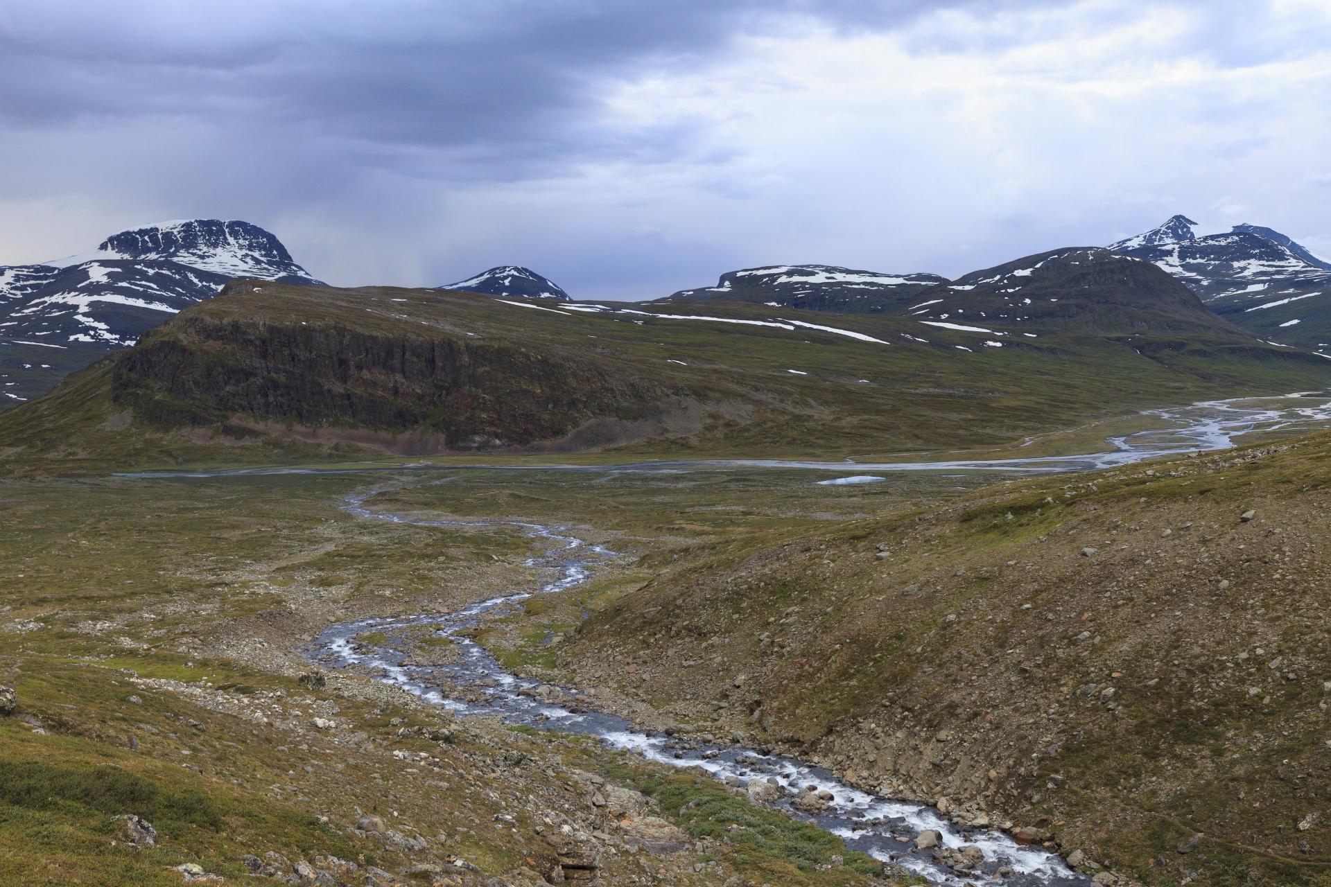 Abendstimmung – ein Blick zurück auf den Tjäktjajåkka, links die Felswand des Mádir (1078m), dahinter der Stuor Ruška (1700m) und neben dem Mádir der Roavgoaivi mit dem Mádirčohkka dahinter und dann am Bildrand ein Hauptgipfel der Sälka Gruppe mi