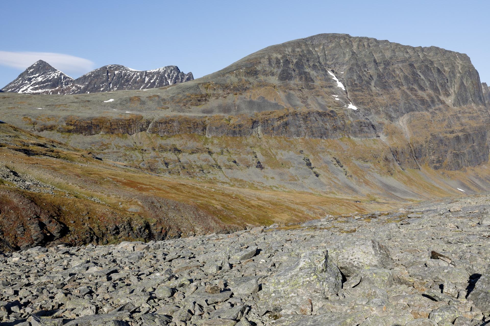 Ein erster Blick auf die Nallo Fjällstuga vor dem mächtigen Nallo, im Hintergrund der Šielmmácohkka